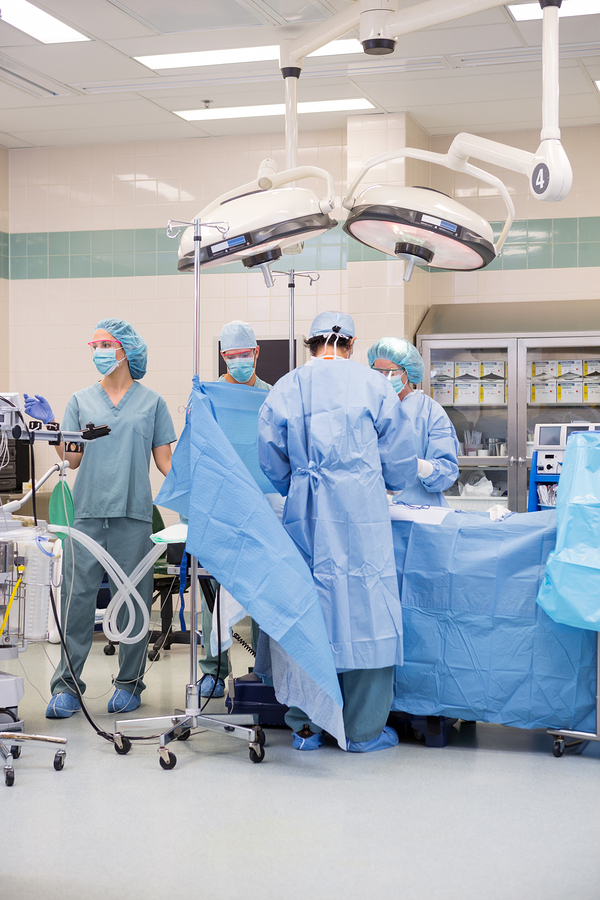 Surgical team operating on patient in theater