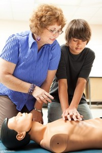 Teacher helping a teenage boy learn how to perform CPR.