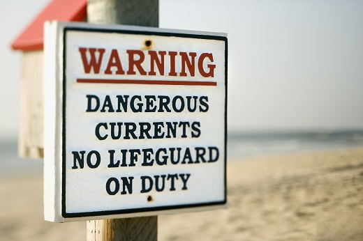 Warning sign on post at the beach with ocean in background.