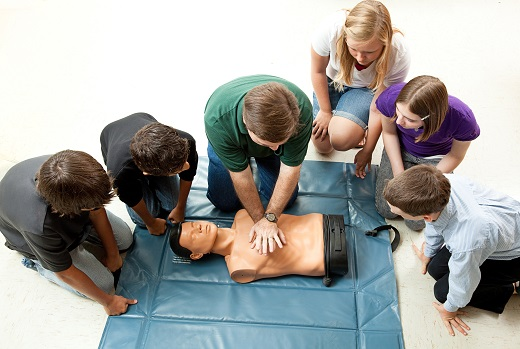 Group of teenagers learing CPR (cardiopulmonary resuscitation) i