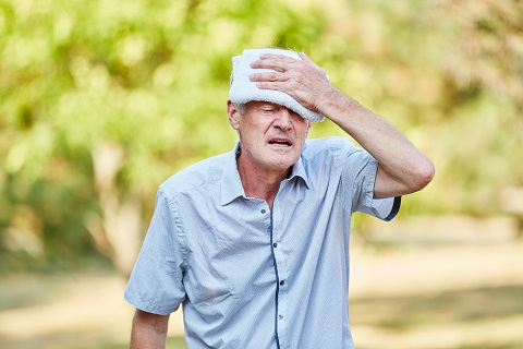 Senior man with heat exhaustion cools his head with wet cloth