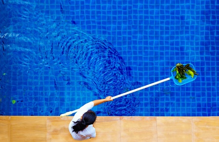 woman personnel cleaning the pool from leaves
